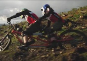 Team work! Husband and wife mountain bikers hurtle over jumps and obstacles on a TANDEM