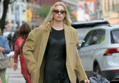 Model Elsa Hosk is seen wearing a black slip dress, camel hair coat and black boots with side bags i